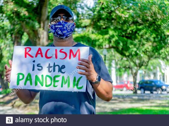a-protestor-waves-a-sign-denouncing-racism-while-at-a-protest-against-police-brutality-june-4-2020-at-memorial-park-in-mobile-alabama-2BX41PM.jpg